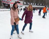 Девушки катаясь на коньках и усмехаясь на парке Стоковая Фотография