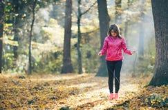 Девушки которые тренируют и слушают к музыке в лесе утра Стоковое Изображение