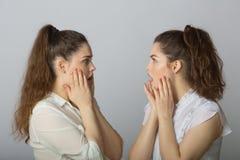 2 девушки красивых сестер двойных с устрашенными сторонами Стоковые Изображения
