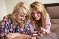 девушки кровати смотря лежа телефон подростковые 2 Стоковые Изображения