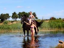 Девушки купают лошадь в озере Стоковые Фотографии RF
