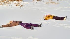 Девушки кладя на снег Стоковая Фотография RF