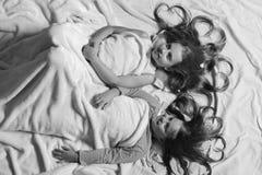 Девушки лежат на белой и розовой предпосылке простынь Дети с счастливыми сторонами и сердца в волосах в кровати стоковые изображения