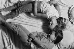 Девушки лежат на белый и розовый гнуть простынь стоковое изображение