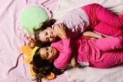 Девушки лежат на белый и розовый обнимать простынь стоковое фото