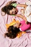 Девушки лежат на белый и розовый щекотать предпосылки простынь стоковые изображения rf