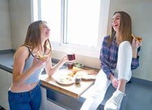 Девушки лучшего друга есть пиццу в кухне Стоковая Фотография RF