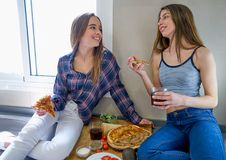 Девушки лучшего друга есть пиццу в кухне Стоковые Фотографии RF