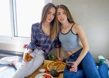 Девушки лучшего друга есть пиццу в кухне Стоковые Изображения RF