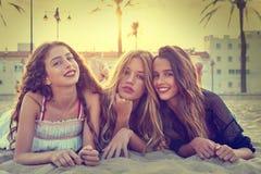 Девушки лучших другов на песке пляжа захода солнца Стоковые Изображения