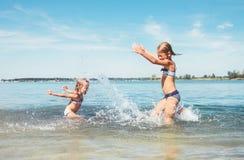 2 девушки маленьких сестры околпачивая вокруг в волнах штиля на море брызгая воду друг к другу Изображение концепции семейного от стоковая фотография