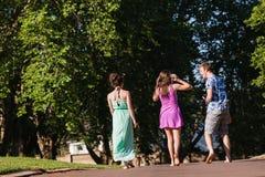 Девушки мальчика идя прочь говоря смех Стоковое Изображение RF