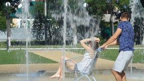 Девушки мальчиков свернули тележки - фонтан в лете акции видеоматериалы