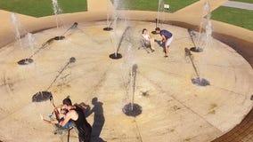Девушки мальчиков свернули тележки - фонтан в лете видеоматериал