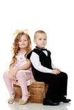 Девушки мальчиков сидят на старом хоботе стоковое изображение rf