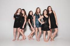 Девушки моды стоя совместно и смотря камеру над серой предпосылкой студии Стоковое Изображение