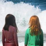 Девушки наблюдают большую аварию волн на береге Калифорнии Стоковые Фото