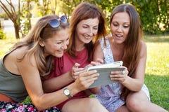Девушки наблюдая фото на таблетке Стоковые Изображения RF