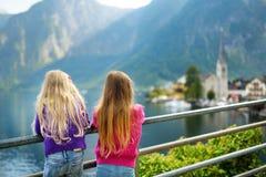2 девушки наслаждаясь сценарным взглядом городка берега озера Hallstatt в австрийских Альпах в красивом вечере освещают на красив Стоковые Изображения RF
