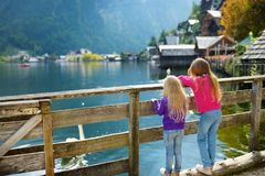 2 девушки наслаждаясь сценарным взглядом городка берега озера Hallstatt в австрийских Альпах в красивом вечере освещают на красив Стоковые Фото