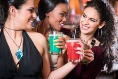 Девушки наслаждаясь ночной жизнью в клубе, выпивая коктеилями Стоковое Фото