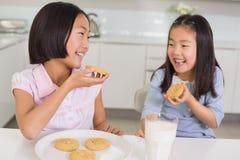 Девушки наслаждаясь печеньями и молоком в кухне Стоковые Фотографии RF