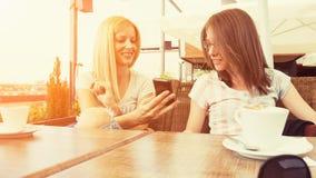 Девушки наслаждаясь сидеть в кафе Стоковые Фото