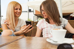 Девушки наслаждаясь сидеть в кафе Стоковое фото RF