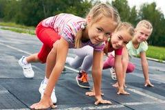Девушки начиная побежать на следе Стоковые Изображения