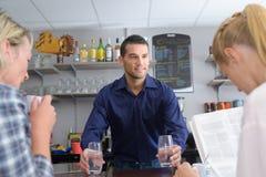 Девушки на баре пока бармен подготавливая коктеиль Стоковое фото RF