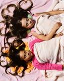 Девушки на белой и розовой предпосылке простынь стоковое фото