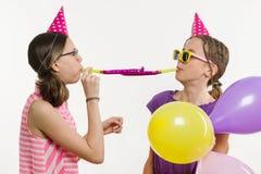 Девушки на белой предпосылке, в праздничных шляпах, дуя в трубах Стоковая Фотография