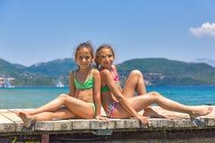 Девушки на деревянной пристани в море Стоковая Фотография