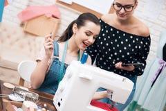 3 девушки на магазине фабрики одежды Они сидят за швейными машинами Стоковое Изображение RF