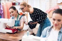 3 девушки на магазине фабрики одежды Они сидят за швейными машинами Стоковое Изображение