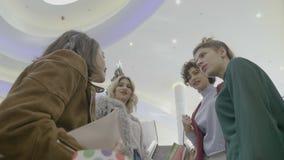 Девушки на моле наслаждаясь gossiping каникул рождества и используя эскалаторы для достижения зоны еды после встречи покупок - видеоматериал
