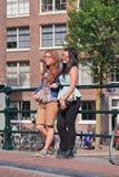Девушки на мосте в старом поясе канала, Амстердаме, Нидерланд Стоковые Фотографии RF