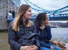 2 девушки на отключении города к Лондону - ослабьте на мосте башни Стоковые Изображения RF