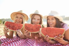 Девушки на партии есть арбуз на пляже стоковое фото