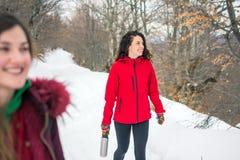 Девушки на пешем отключении на снежной горе Стоковая Фотография