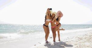 Девушки на пляже принимая фото Selfie на телефоне клетки умном, жизнерадостных женщинах в бикини принимая соломенные шляпы на лет