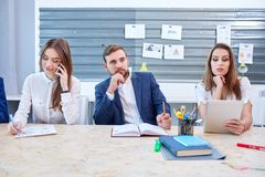 2 девушки на работе в офисе, и взгляды человека в расстояние Стоковые Фото