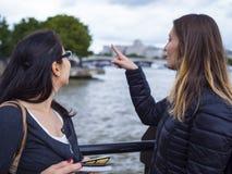 2 девушки на реке Темзе в Лондоне исследуют город Стоковое фото RF