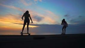 2 девушки на скейтбордах едут на дороге против утеса и небе во время захода солнца сток-видео