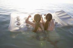 Девушки на тюфяке воздуха плавая на воду Стоковое Изображение RF