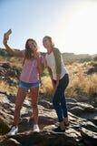 Девушки на утесе принимая selfies Стоковые Изображения RF
