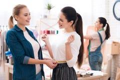 3 девушки на фабрике одежды Одно из их измеряет другое одно Стоковое Изображение