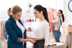 3 девушки на фабрике одежды Одно из их измеряет другое одно Стоковое Изображение RF