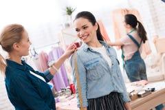 3 девушки на фабрике одежды Одно из их измеряет другое одно Стоковая Фотография