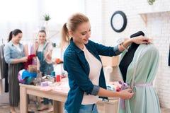 3 девушки на фабрике одежды Одно из их измеряет новое платье Стоковые Фото